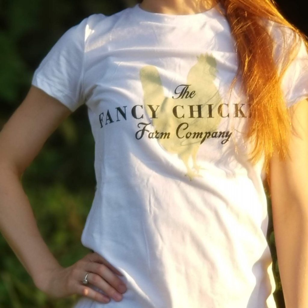 women wearing a white fancy chicken farm co t-shirt